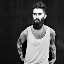 Mann mit BART und coolen undercut Frisur mittlerer Länge