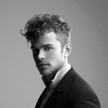 Mann mit Mittel-kurzen lockigen fade Haarschnitt moderne