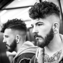 Mann mit dem lockigen undercut Frisur mittlerer Länge