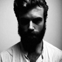 Mann mit langen und lockigen Haarschnitt