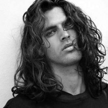 Mann mit sehr langen lockigen Haaren
